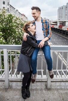 Liefdevol paar staande op de brug in de grote stad