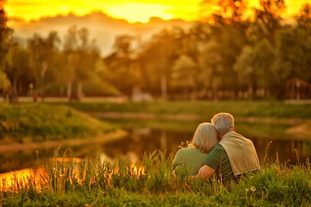 Liefdevol volwassen stel in zomerpark aan de zonsondergang