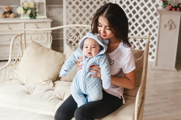 Liefdevolle aziatische moeder bedrijf baby zoon thuis.