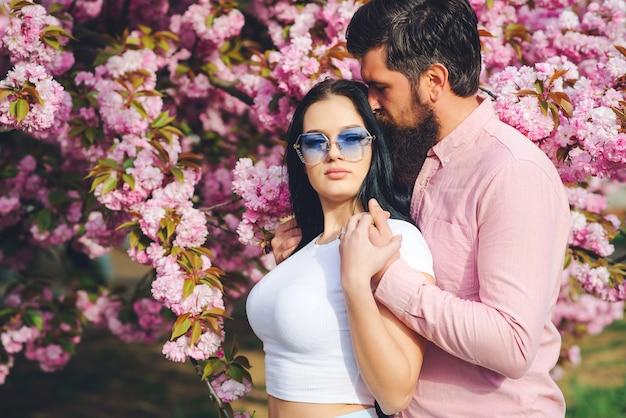 Liefdevolle bebaarde man en vrouw in een voorjaar park. lente roze sakura bloesem. mooie vrouw en haar knappe vriendje buitenshuis knuffelen.