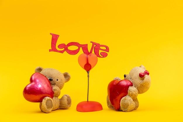 Liefdevolle beer speelgoed concept. woord liefde hart. teddy bear loving schattig, zittend op gele achtergrond. valentijnsdag conceptstijl. creatieve wenskaart.