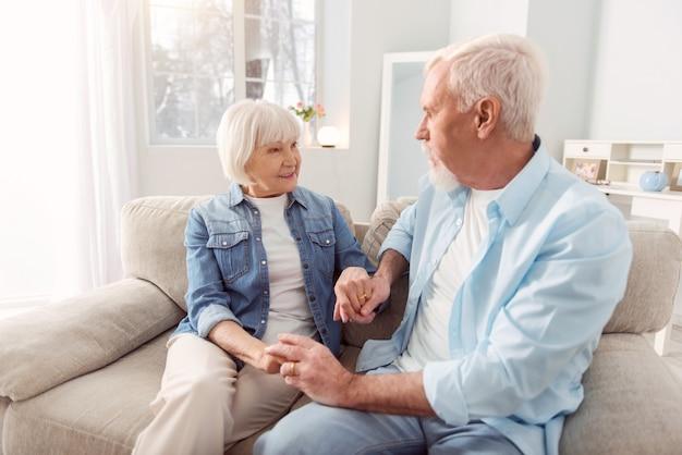 Liefdevolle blikken. lieve bejaarde echtpaar zittend op de bank en hand in hand terwijl ze elkaar bewonderend en glimlachend aankijken