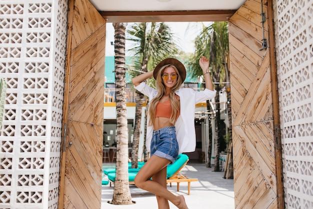Liefdevolle blootsvoets vrouw in stijlvolle kleding dansen in hete zomerdag. openluchtportret van leuke blonde vrouw in denimborrels die haar hoed met glimlach aanraken.