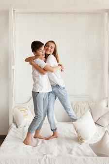 Liefdevolle broer en zus omarmen thuis op bed