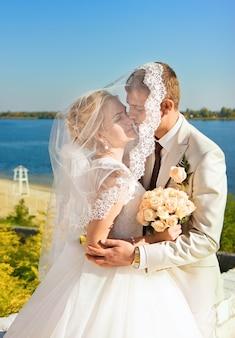 Liefdevolle bruid en bruidegom beschutte sluier bruid omhelzing op de oever van de rivier