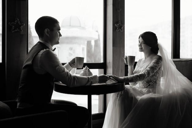 Liefdevolle bruid en bruidegom zitten in een café. het drinken van thee hand in hand. liefde, bruiloft concept. gelukkig pasgetrouwde stel.