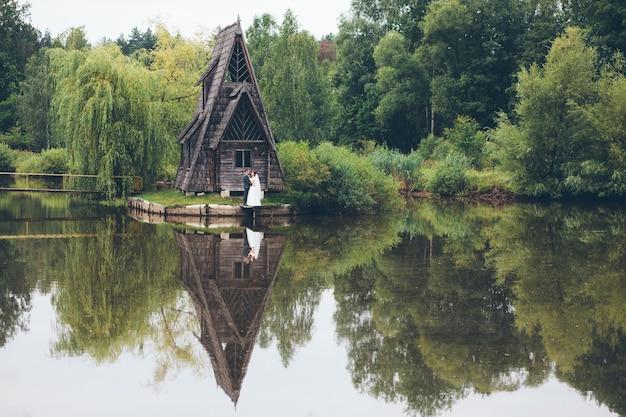 Liefdevolle bruidspaar in de buurt van een mooi huis aan het meer in het bos