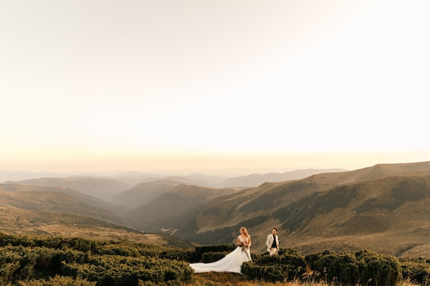 Liefdevolle bruidspaar knuffelen teder tegen de bergen, romantische relatie, prachtig landschap.