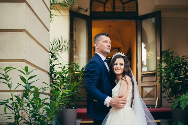 Liefdevolle bruidspaar knuffelen tegen de achtergrond van een prachtige stad