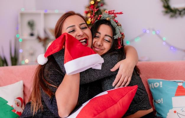 Liefdevolle dochter en moeder knuffelen elkaar zittend op de bank genieten van kersttijd thuis