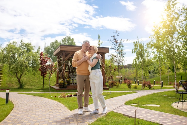 Liefdevolle echtgenoot die zijn vrouwelijke echtgenoot buitenshuis knuffelt