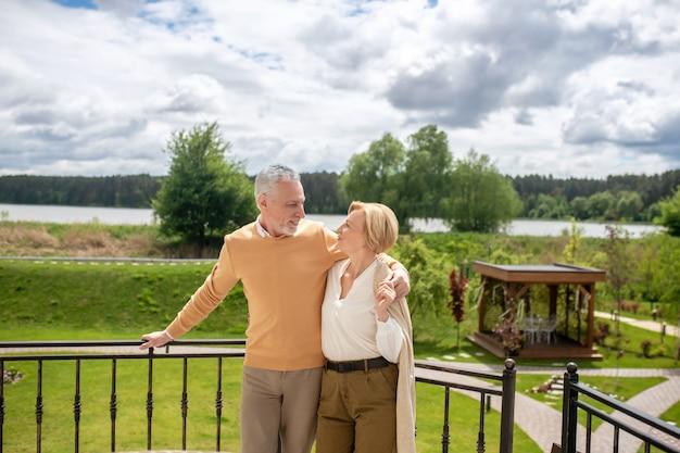 Liefdevolle echtgenoot en zijn elegante vrouw staan op het terras