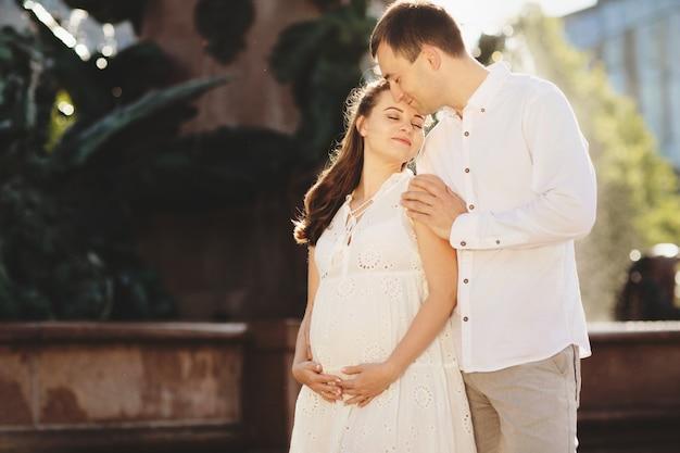 Liefdevolle echtgenoot knuffelt zachtjes zijn zwangere vrouw