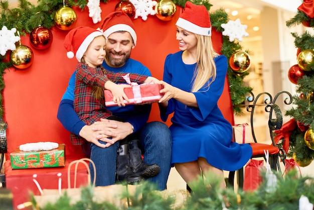 Liefdevolle familie met geschenken in winkelcentrum