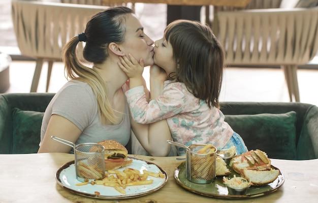 Liefdevolle familie. moeder met schattige dochter fastfood eten in een café, familie en voeding concept