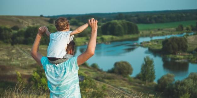 Liefdevolle familie. vader en zijn zoon babyjongen buiten spelen en knuffelen. gelukkige vader en zoon buitenshuis. concept van vaderdag.