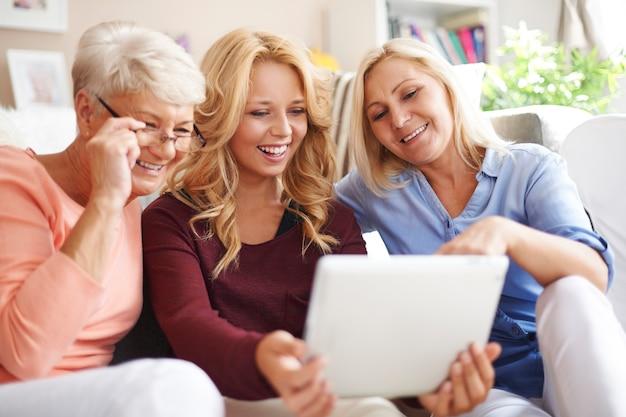Liefdevolle familie van vrouwen met behulp van digitale tablet
