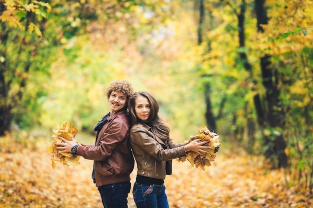 Liefdevolle gelukkige paar in de herfst in park herfst esdoorn bladeren in handen houden
