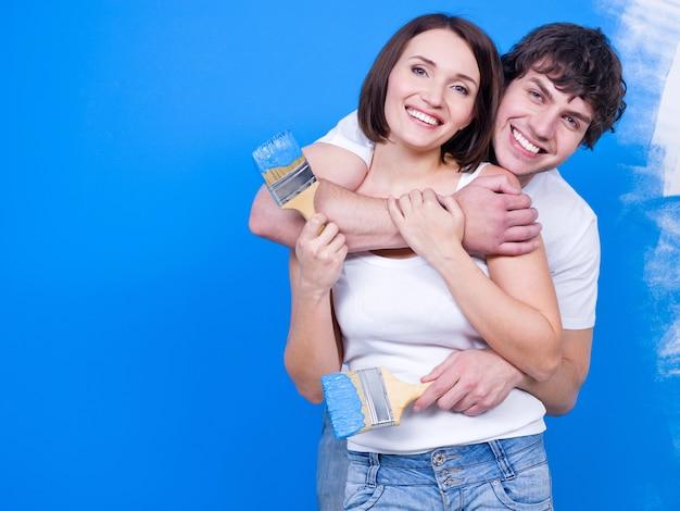 Liefdevolle gelukkige paar staande in omhelzing met penseel in de buurt van de muur