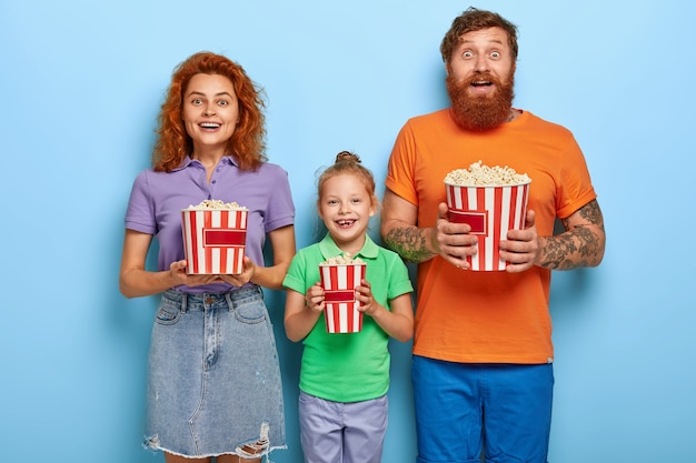 Liefdevolle gemberfamilie poseren met popcorn
