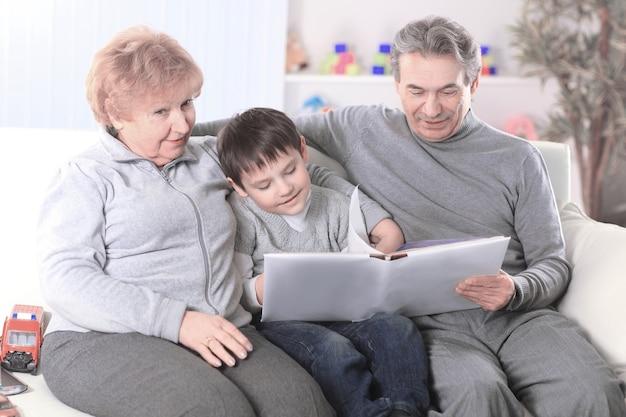 Liefdevolle grootouders met kleinkind zittend op de bank.