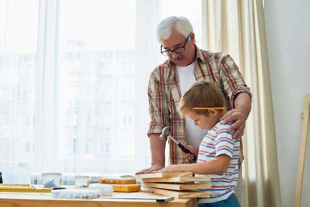 Liefdevolle grootvader en kleine jongen samen houten modellen maken