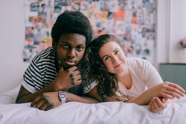 Liefdevolle interracial paar liggend op bed.
