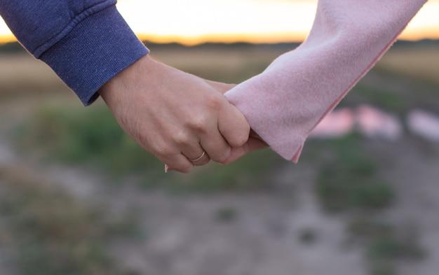 Liefdevolle jong koppel hand in hand. handen van een meisje en een jongensclose-up.