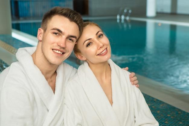 Liefdevolle jong koppel in badstof gewaden ontspannen bij het zwembad samen