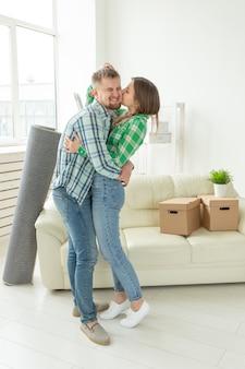 Liefdevolle jong koppel omarmen vreugde in het verhuizen naar hun nieuwe huis het concept van verhuizen en