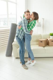Liefdevolle jong koppel omarmen vreugde in verhuizing naar hun nieuwe huis