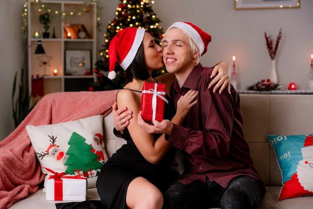 Liefdevolle jong koppel thuis in de kersttijd met kerstmuts zittend op de bank in de woonkamer die geschenken ontvangt