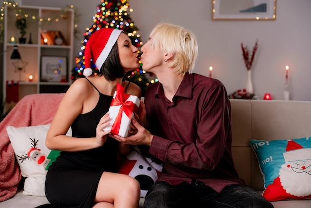Liefdevolle jong koppel thuis in de kersttijd zoenen en het dragen van kerstmuts zittend op de bank in de woonkamer.