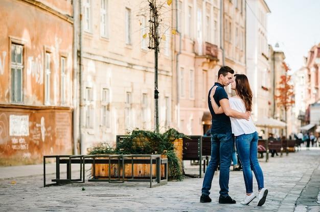 Liefdevolle jong koppel zoenen en knuffelen in st valentijnsdag in de stad. liefde en tederheid, dating, romantiek, familie, jubileumconcept.