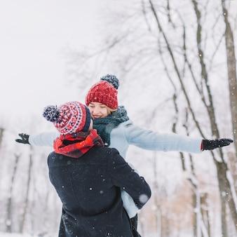 Liefdevolle jong stel in de winter sneeuwval