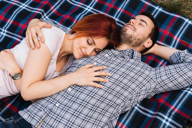 Liefdevolle jong stel samen slapen op deken