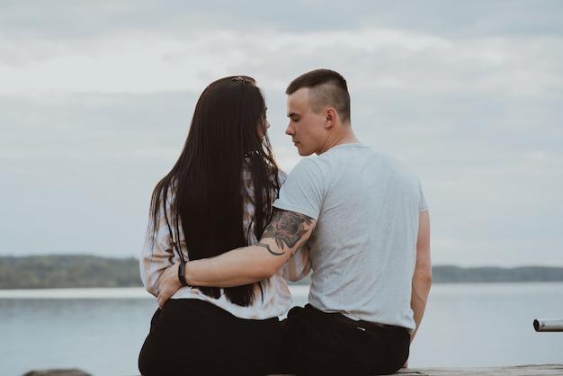 Liefdevolle jonge gelukkige paar knuffelen op het strand aan de rivier gedurende de dag