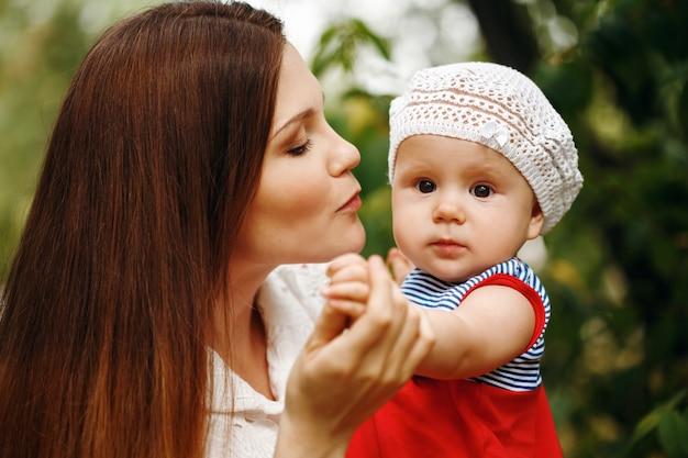 Liefdevolle jonge moeder die haar baby vasthoudt en kust