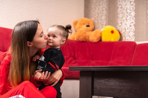 Liefdevolle jonge moeder die haar dochtertje kust als ze haar knuffelt