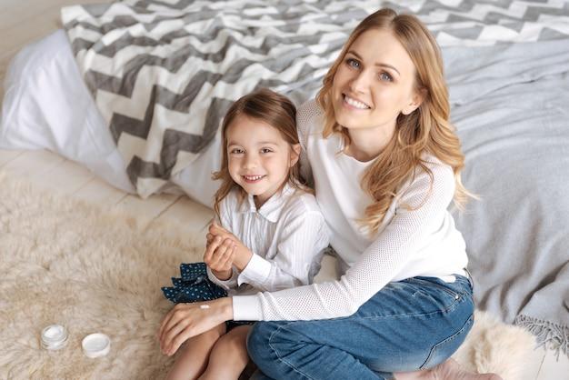 Liefdevolle jonge moeder die haar schattige dochtertje met één hand omhelst en aan de andere kant wat crème heeft, terwijl zowel moeder als kind op het tapijt zitten en glimlachen