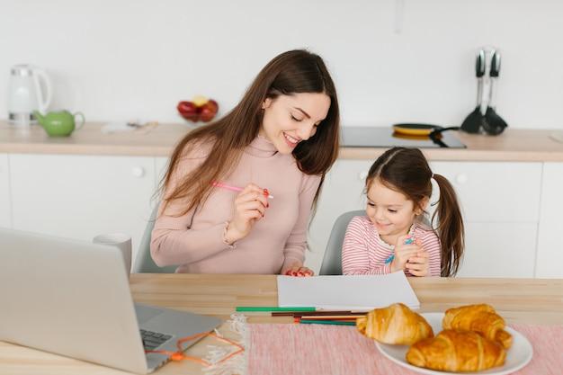 Liefdevolle jonge moeder en kleine kleuter dochter zitten aan tafel samen tekenen op papier