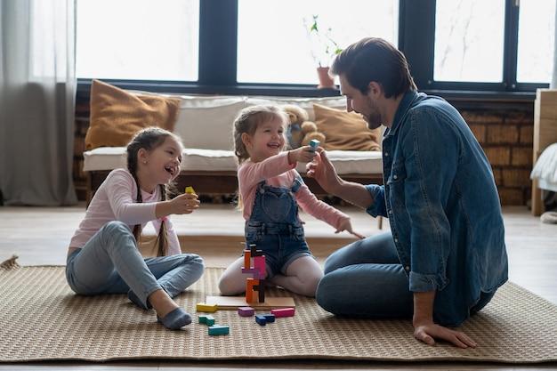 Liefdevolle jonge vader liggend op de vloer met kleine kinderen veel plezier bezig met grappige activiteiten met bouwstenen, zorgzame vader spelen met kleine kinderen bouwen met blokken geniet samen van tijd thuis