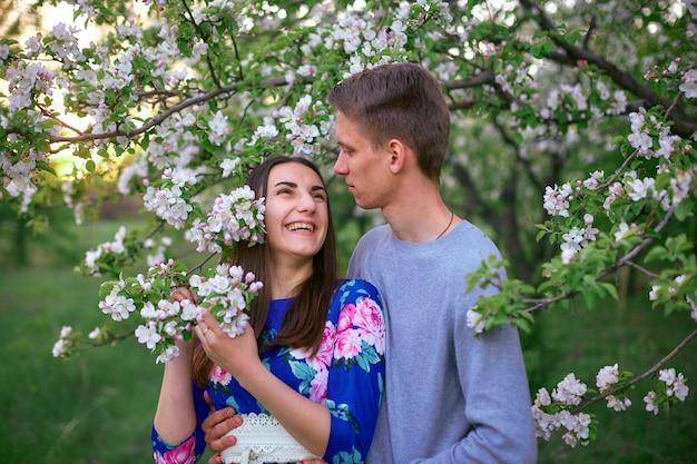 Liefdevolle jongen en meisje in een bloeiende appelboomgaard bij zonsondergang