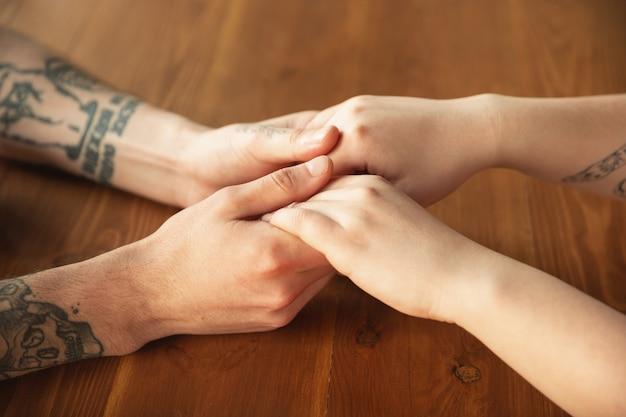 Liefdevolle kaukasisch paar hand in hand close-up op houten muur. romantisch, liefde, relatie, teder ontroerend. ondersteunende en helpende hand, familie, warm. saamhorigheid, gevoel en emoties. Premium Foto