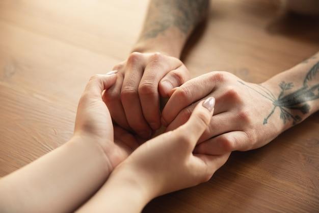 Liefdevolle kaukasisch paar hand in hand close-up op houten muur.