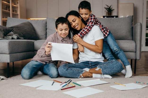Liefdevolle kleine jongens hebben een tekening gemaakt voor hun moeder en laten zien, moeder is blij en opgetogen. hoge kwaliteit foto