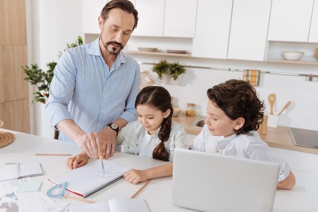 Liefdevolle kleine schoolkinderen die aandachtig luisteren naar hun jonge vader die geometrie uitlegt en een cirkel schrijft met een passer