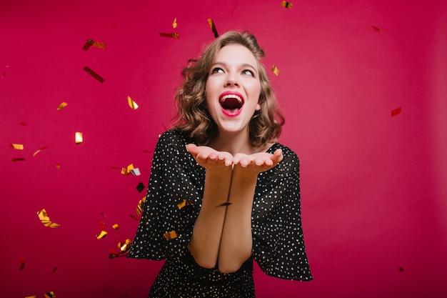 Liefdevolle kortharige meisje positieve emoties uitdrukken op feestje met confetti