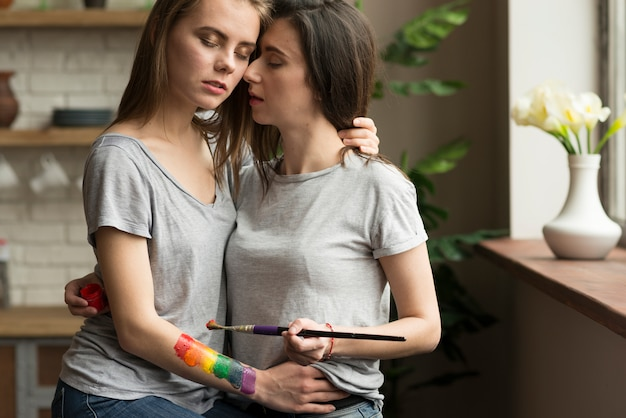 Liefdevolle lesbische jong koppel met penseel en geschilderde regenboogvlag aan kant