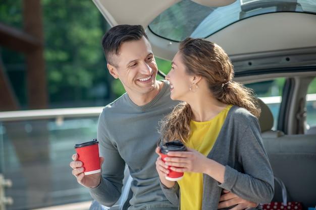 Liefdevolle man en vrouw koffie drinken in de buurt van de auto